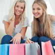 Smiling girls looking at the camera with bags by their feet — Stock Photo