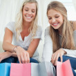 Smiling girls looking into the bags below them - Stock Photo