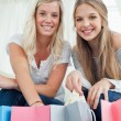 Stock Photo: Girls smiling as they look at camerwith bags