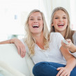 Laughing sisters sitting on the couch — Stock Photo