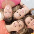 Four girls smiling as they lie on the floor together — Stock Photo