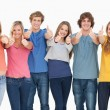 Stock Photo: Six friends giving thumbs up as they smile