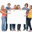 Smiling group of with a blank space as they point to it — Stock Photo #13962682