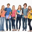 Stock Photo: Smiling students wearing backpacks and holding books in their ha