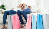 A couple of girls sitting after a hard day of shopping — Stock Photo