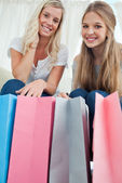 Close of bags with girls above them smiling — Stock Photo