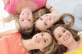 Vier meisjes glimlachen als ze op de vloer samen liggen — Stockfoto
