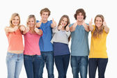 Six friends giving thumbs up as they smile — Stock Photo