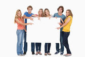 Smiling group of with a blank space as they point to it — Stock Photo