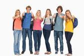 Sırt çantaları giyer gibi bir başparmak vazgeçerek grup gülümseyen — Stok fotoğraf