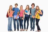 öğrencilerin giymiş sırt çantaları ve tutan gülümseyerek kitaplar onların ha — Stok fotoğraf