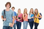 A man standing in front of his friends as he smiles — Stock Photo