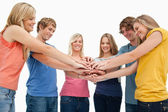 Low angle shot of friends smiling and looking at their hands sta — Stock Photo