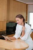 Mulher segurando um copo enquanto olha para um computador tablet — Fotografia Stock
