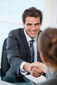 Businessman shaking hands with a client while smiling — Stock Photo