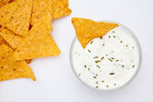 Bowl of dip with herbs with a nacho dipped in it — Stock Photo