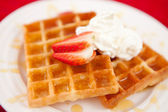 Waffles with whipped cream and strawberry and syrup — Stock Photo
