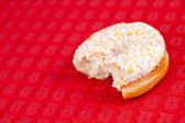 Half doughnut on a red tablecloth — Stock Photo