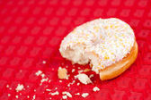 Half eaten doughnut on a red tablecloth — Stock Photo