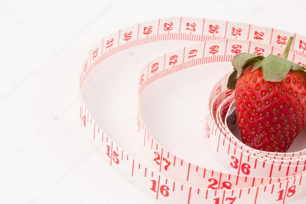 Close up of a strawberry surrounded by a ruler against a white background — Stock Photo #13968620