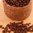 Close up of a basket filled with coffee seeds on a wooden tablec - 