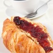 Coffee cup behind a croissant — Photo