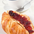 Coffee cup behind a croissant — Stock Photo