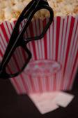 ポップ コーンのボックスの端にぶら下がっているメガネ — ストック写真