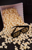 3D glasses on falling pop corn out of a box — Stock Photo
