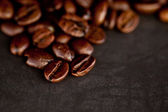 Dark blurred coffee seeds laid out together on a black table — Stock Photo