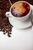 Black coffee and milk with beans — Stock Photo