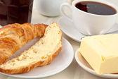 Tereyağı ile yayılan bir kruvasan ile kahvaltı — Stok fotoğraf