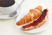 Croissant next to a coffee cup — Stock Photo