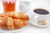 Croissants and a cup of coffee on white plates with sugar milk a — Stock Photo
