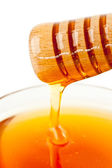 Honey sticky trickle on a dipper dropping in a honey bowl — Stock Photo