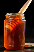 Honey full jar with a honey dipper — Stock Photo
