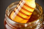 Cazo miel saliente un tarro — Foto de Stock
