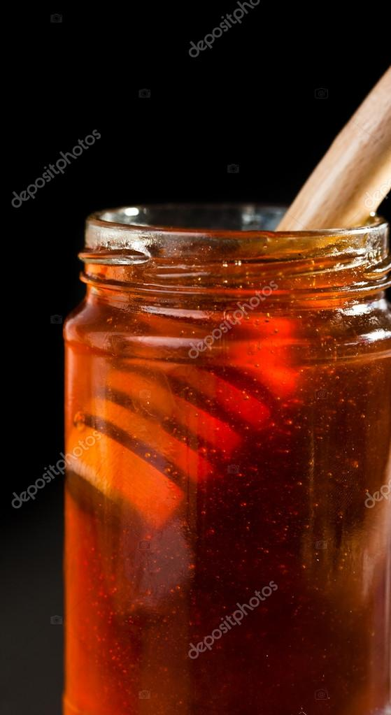 Close up of a honey jar with a honey dipper against a black bakground — Stock Photo #13989956
