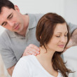 Smiling woman sitting while being massaged by a man — Stock Photo
