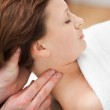 Therapist massaging the neck of woman while holding her head — Stock Photo #13994517