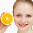 Close up of a smiling woman presenting an orange — Stock Photo