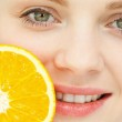 Close up of a woman placing an orange near her lips — Stock Photo