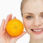 Fair-haired woman holding an orange — Stock Photo