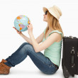 Woman sitting while holding a world globe — Stock Photo