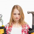 Serious woman holding a hammer and and a wrench - Stock Photo