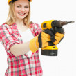 Woman using an electric screwdriver while smiling — Stock Photo #13996523