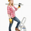 Woman holding a spirit level next to a step ladder — Stock Photo #13996539