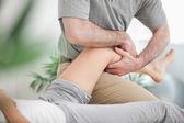 Człowiek manipulowania nogi kobiety, podczas gdy ona leży — Zdjęcie stockowe