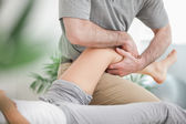 Man manipulating the leg of a woman while she is lying — Stock Photo