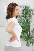 Woman touching her back while looking away — Stock Photo
